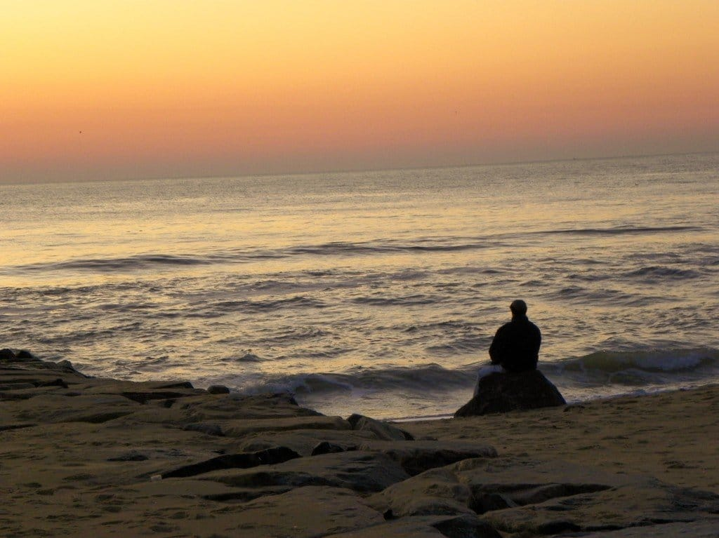 Man siting on rock Ocean City,MD sunrise Nov 2009